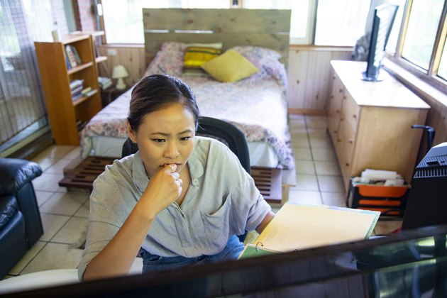 A young woman in her home office with a worried expression.