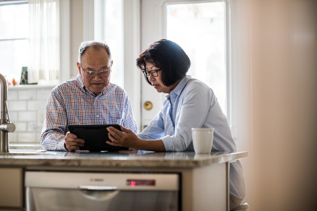 Senior couple using tablet on couch at home