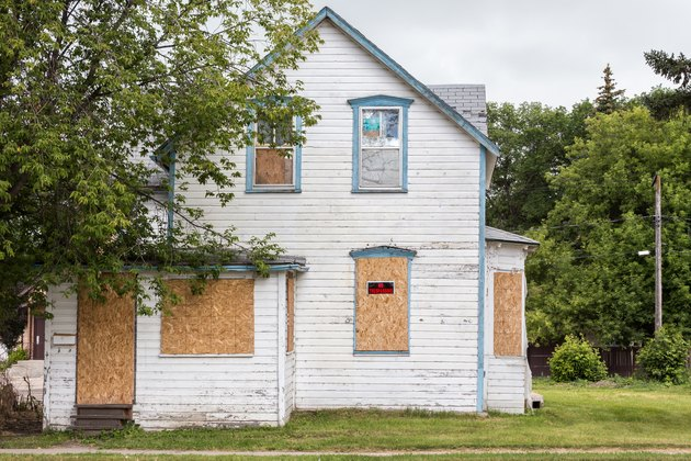 How to Find Foreclosed Homesold condemned white two-story house with windows boarded up