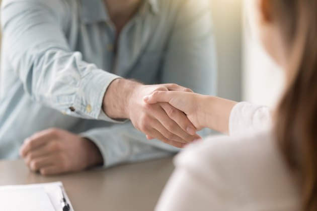 Business agreement handshake of man and woman at the office