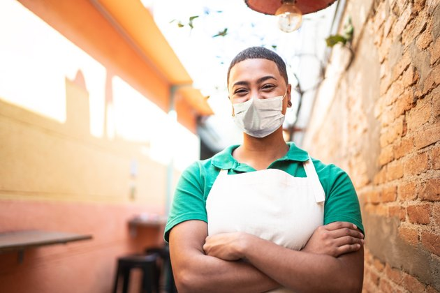Portrait of young waitress working in a coffee shop using protective mask