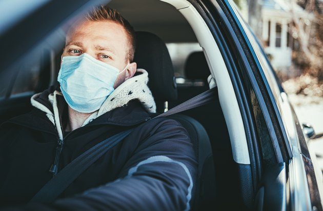 COVID-19, Young man wearing disposable face mask while driving