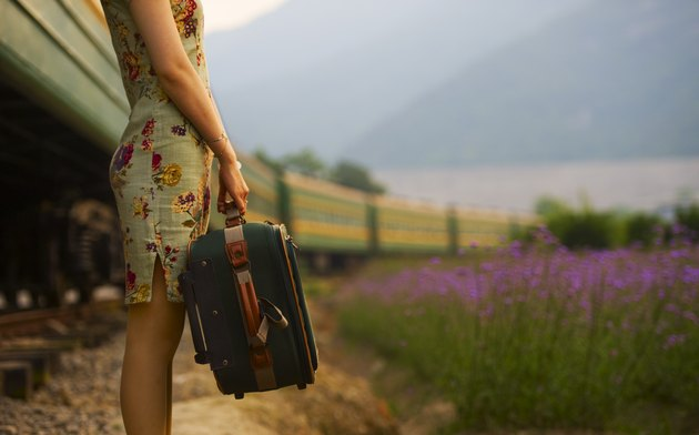 Young woman carrying luggage in old retro vintage train