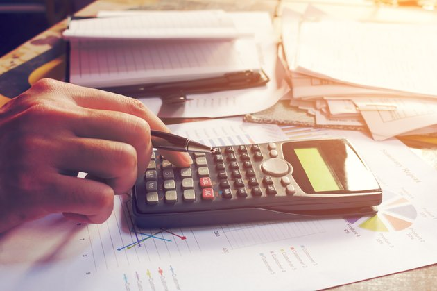 Close up man using calculator and doing finance in home