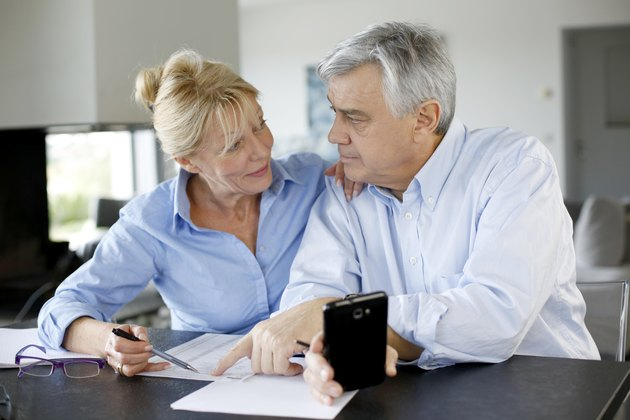 Senior couple checking accounts with smartphone in house