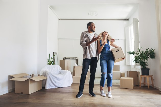 Full length of couple laughing while standing in new home