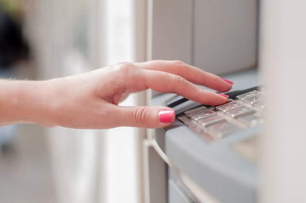 Close up of hand entering pin at an ATM.