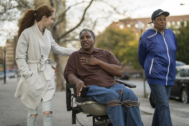 teenage girl talking and walking with a woman and a disabled man in wheelchair