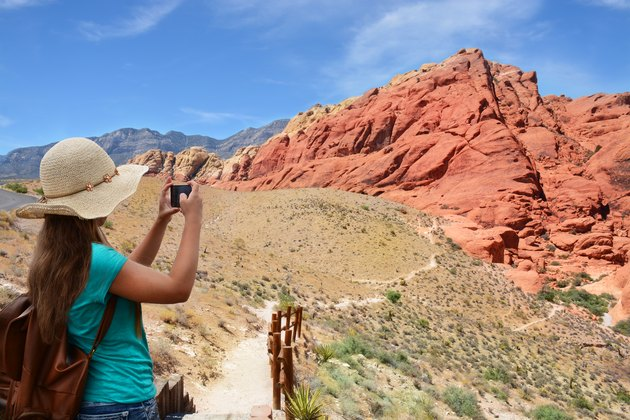 Girl taking photo with her smartphone on hiking trip.