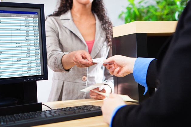 Bank Teller Working with Customer at Bank Counter in Retail Bank