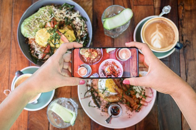 Woman photographing brunch meal in a cafe with smartphone, Mexico