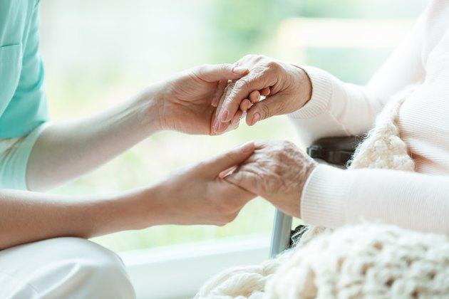 Nurse holding patient's hands