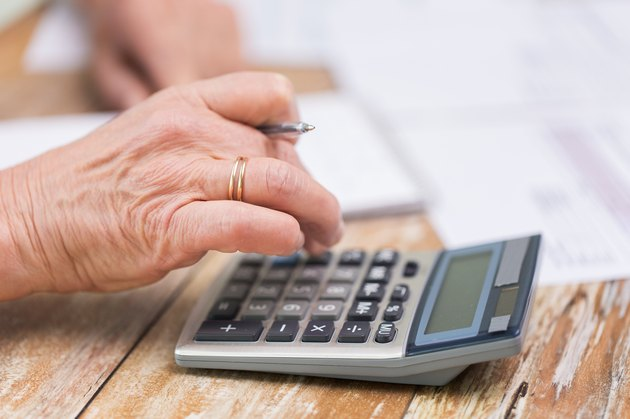 close up of senior woman counting with calculator