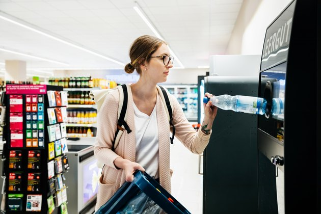 Young Woman Recycling Bottles At The Supermarket