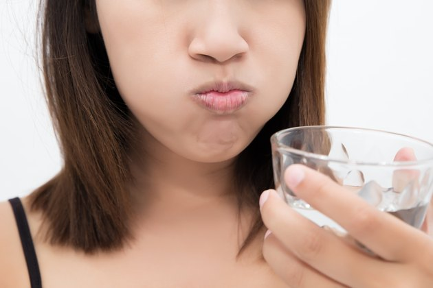 Healthy happy woman rinsing and gargling while using mouthwash from a glass, During daily oral hygiene routine, Portrait with bare shoulders, Dental Health Concepts