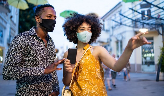 Afro Couple wearing protective face mask walking on the streets and using smart phone, during COVID-19