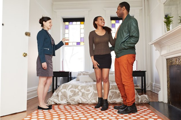 Realtor showing apartment bedroom to couple