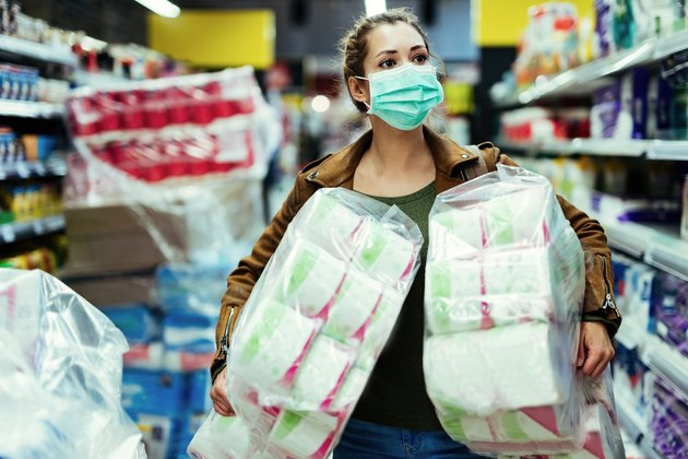Woman with face mask buying toilet paper in supermarket during virus epidemic.
