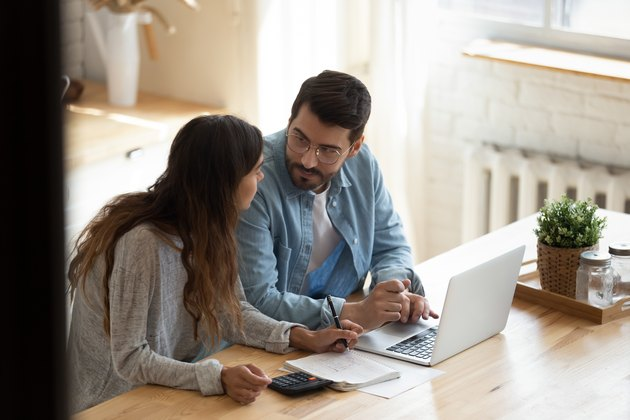 Focused family couple discussing monthly expenses, using computer banking applications.