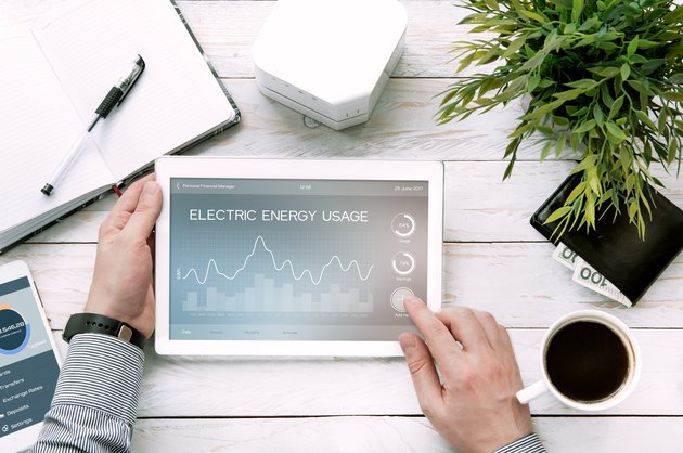 Man holds tablet pc with electric energy usage application.