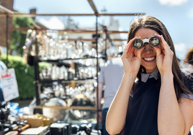 UK, London, Portobello Road, portrait of laughing woman looking through old binoculars