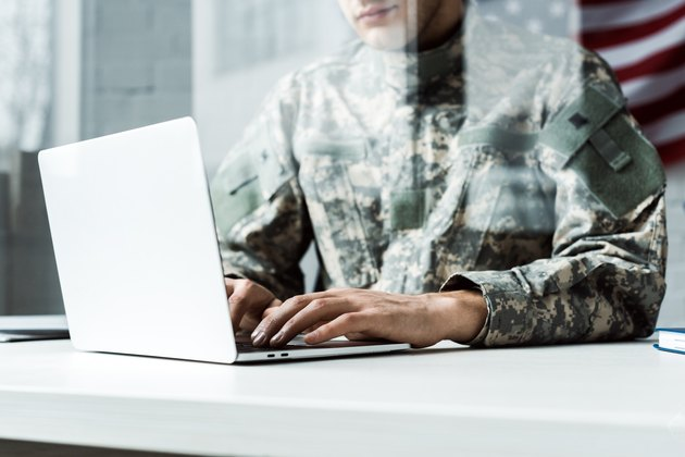 cropped view of soldier in camouflage uniform using laptop