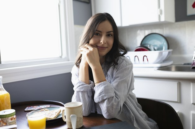 Portrait confident young Latinx woman eating breakfast in kitchen