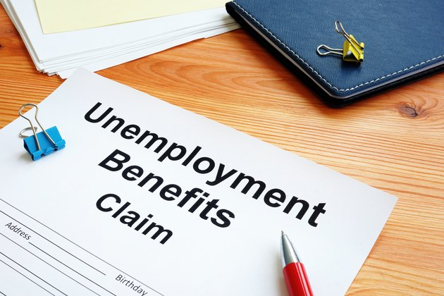 Unemployment benefits claim and stack of documents.
