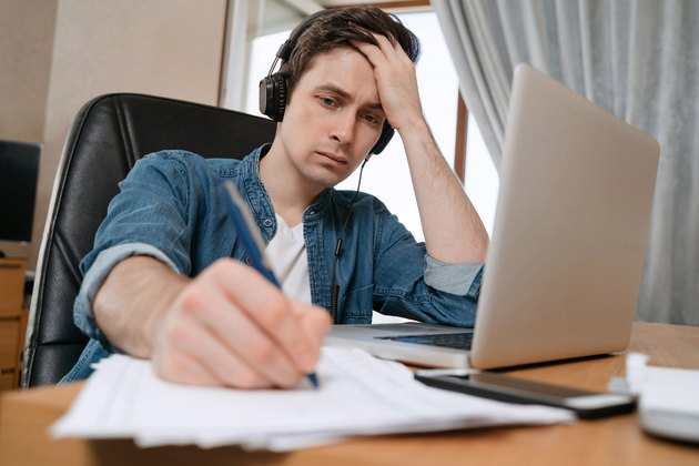 Freelancer wearing headphones working remotely with laptop