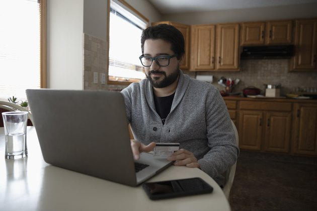 Latinx man with credit card online shopping at laptop in kitchen