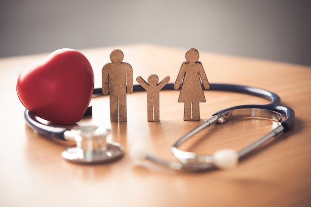 Medical Insurance Concept With Family  And Stethoscope On Wooden Desk