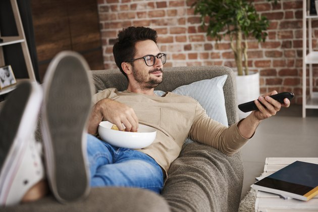 Content man lying on couch at home with bowl of potato chips watching TV