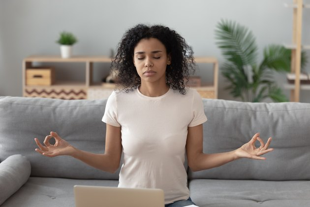 Focused black woman meditating on sofa at home