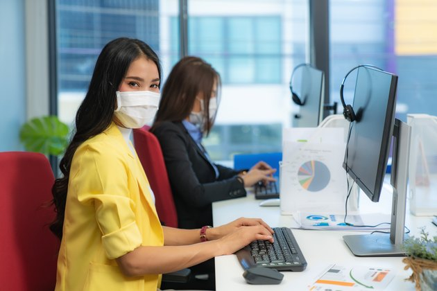 Businesswoman or office worker are working and wear mask for protect Covid-19 or coronavirus disease for New normal and social distance concept in office.
