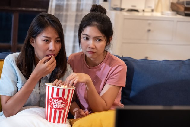 Happy asian lesbain couple watching scary movie on television together and eating popcorn at sofa in night time at home with chill ing emotion.woman friendship lifestyle