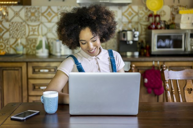 Portrait of a young afro woman surfing the net in the kitchen