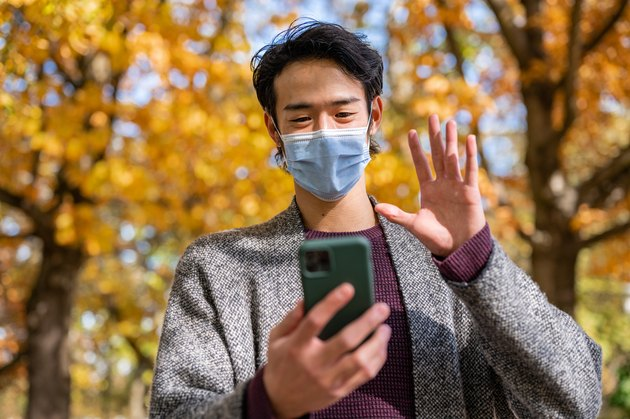 Portrait of young man smiling behind the mask while using a mobile phone