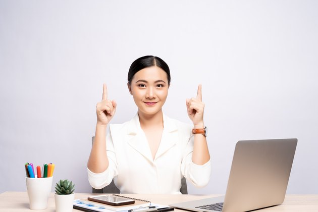 Portrait of businesswoman gesturing while sitting at desk against white background