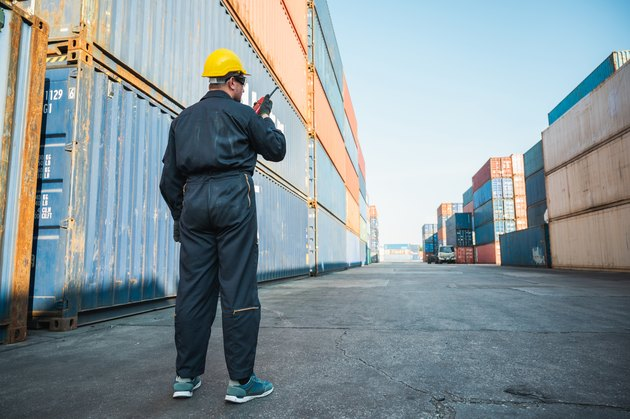 Foreman worker working checking at Container cargo harbor holding radio walkie-talkie to loading containers. Dock male staff business Logistics import export shipping concept.