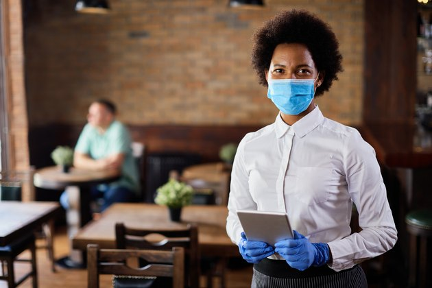 African American waitress wearing protective face mask and gloves while working in cafe.