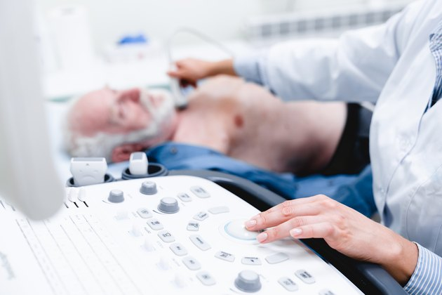 Woman doctor scanning vessels on the neck with ultrasound device scan. Selective focus