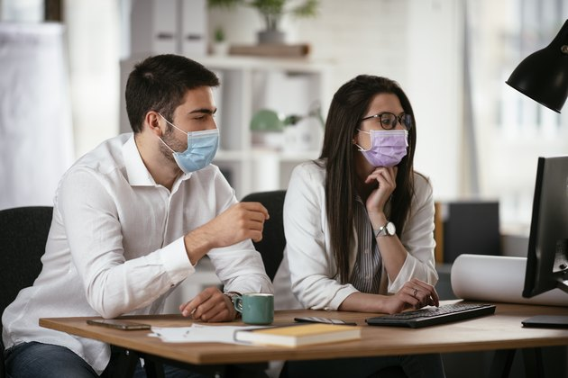 Businessman and businesswoman with medical mask working in the office.