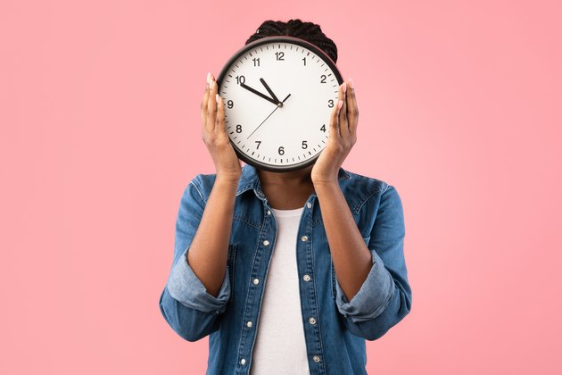 African Girl Holding Clock In Front Of Face, Pink Background