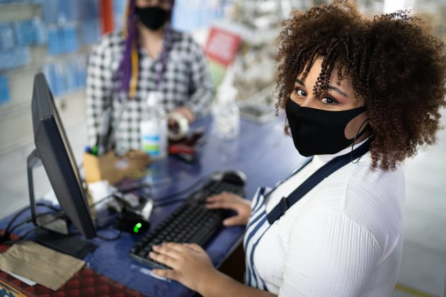 Portrait of cashier wearing face mask working in a store