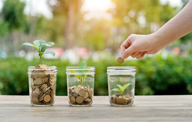 Woman putting coin in the jar with plant