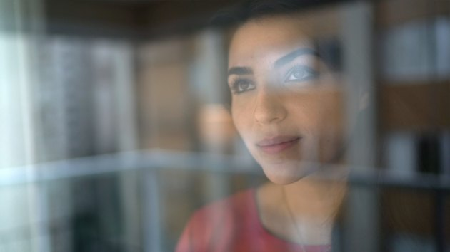 Young woman looking through window