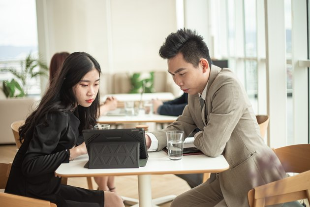 Asian office white collar workers taking a coffee break at the office cafeteria having discussion