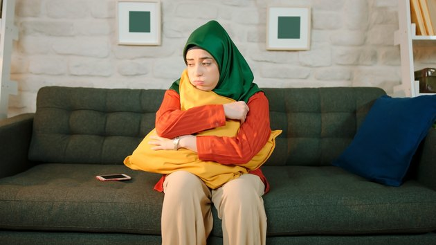 Unhappy young woman sitting on sofa at home wearing a turban. The woman is hugging the pillow.