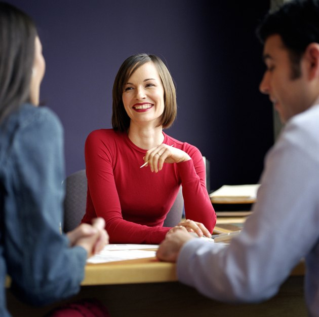 Woman meeting with young couple at desk, focus on woman