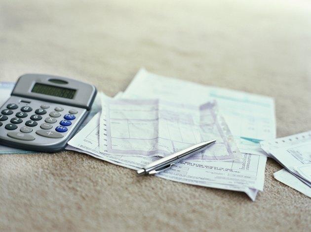 calculator and a ballpoint pen on bills